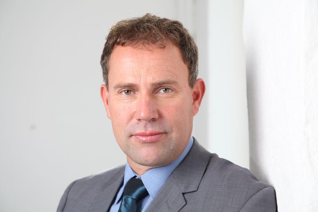 Vergrößern: Nils Lahmann trägt auf diesem Business Portrait Anzug und Krawatte.