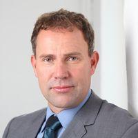 Nils Lahmann trägt auf diesem Business Portrait Anzug und Krawatte.