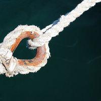 Ein verschlissenes Seil mit einem rostigen Ring hängt über dem Wasser, von oben gehalten von einem dünneren, intaktem Seil.