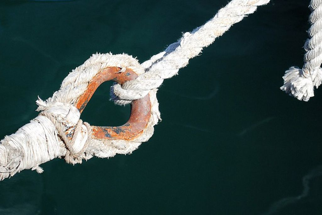 Vergrößern: Ein verschlissenes Seil mit einem rostigen Ring hängt über dem Wasser, von oben gehalten von einem dünneren, intaktem Seil.