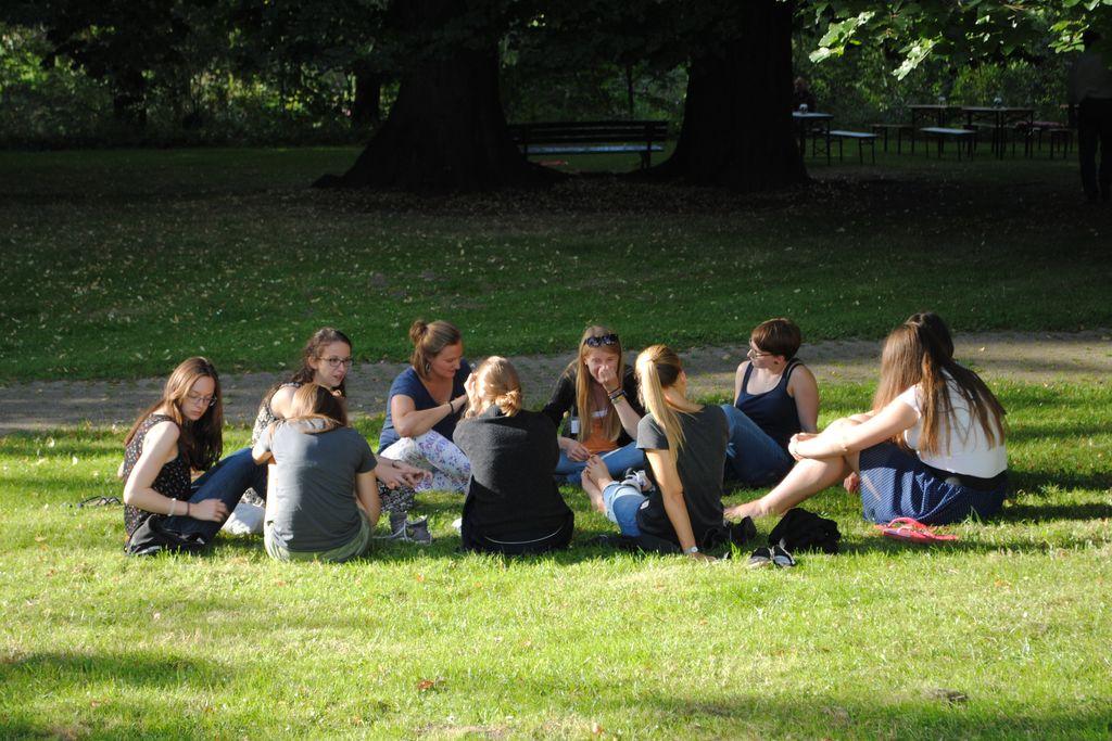 Vergrößern: Studentinnen sitzen im Kreis auf einer Wiese