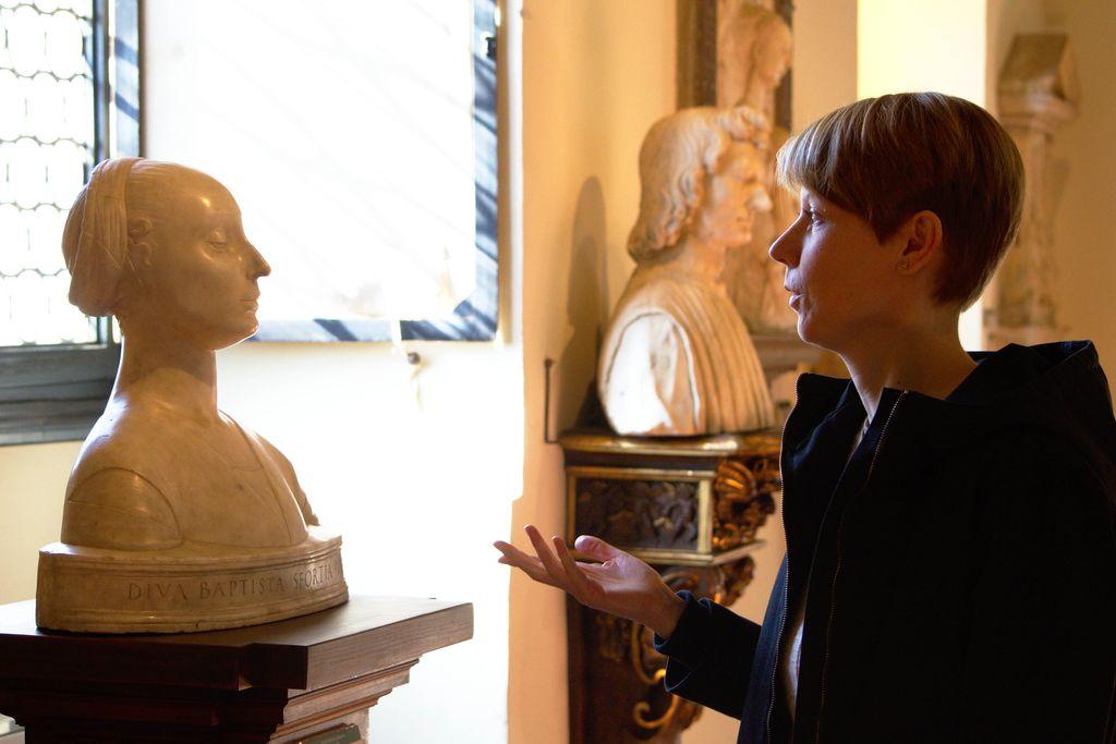 Vergrößern: Eine weiße Büste und rechts daneben Julia Franz mit kurzen blonden Haaren, die auf die Büste schaut