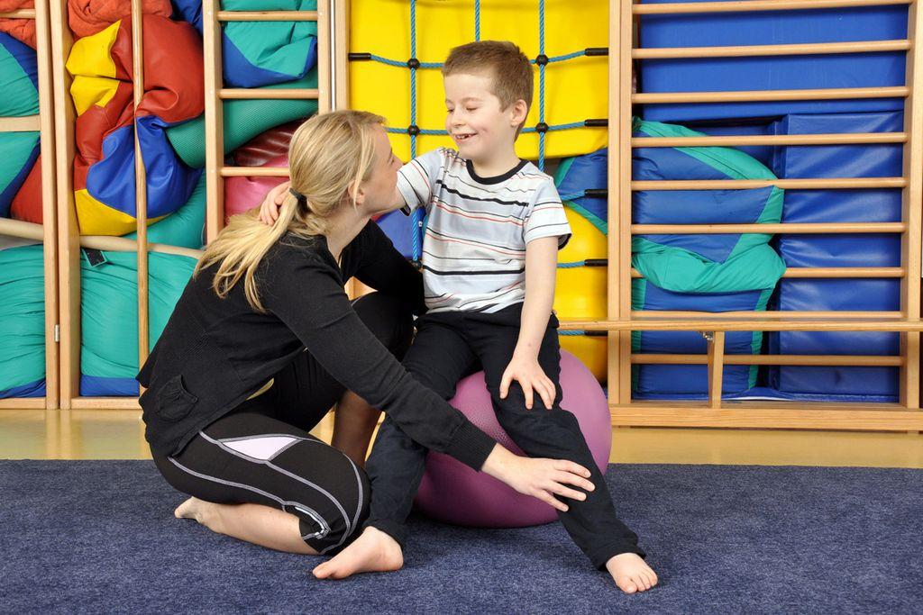Vergrößern: Eine Physiotherapeutin hat ihre Hand platziert auf dem Unterschenkel eines kleinen Jungen, der auf eine Medizinball sitzt. Sie zeigt ihm Übungen.