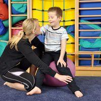 Eine Physiotherapeutin hat ihre Hand platziert auf dem Unterschenkel eines kleinen Jungen, der auf eine Medizinball sitzt. Sie zeigt ihm Übungen.