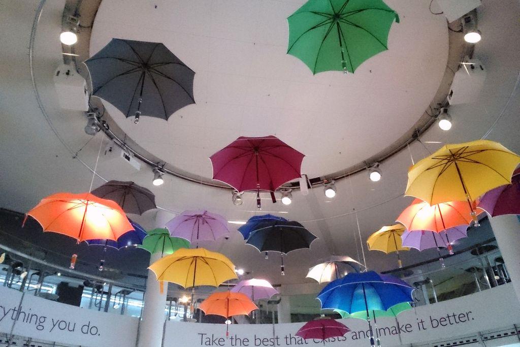 Vergrößern: Bunte Regenschirme hängen von einer Decke herunter
