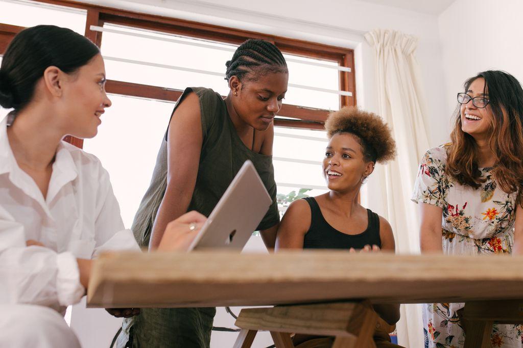Vergrößern: vier junge Menschen unterschiedlicher Hautfarbe diskutieren an einem Tisch