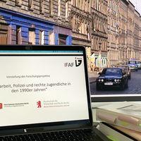 Ein Laptop auf dessen Bildschirm der Projektname steht, rechts daneben ein Bücherstapel