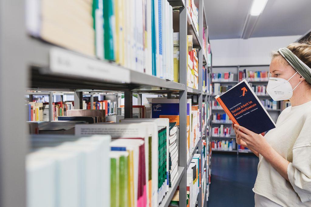 Vergrößern: Eine Frau steht mit Mundschutz vor einem Bücherregal und liest in einem Buch