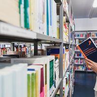 Eine Frau steht mit Mundschutz vor einem Bücherregal und liest in einem Buch