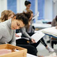 Eine Studentin schreibt etwas auf einem Tisch vor ihr, im Hintergrund liegt eine PErson auf einer Liege