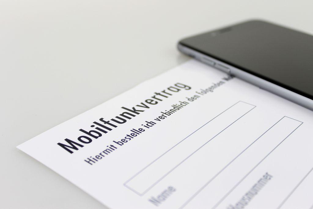 Vergrößern: Ansicht eines Mobilfunkvertrag-Formulares, daneben liegt ein Smartphone