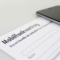 Ansicht eines Mobilfunkvertrag-Formulares, daneben liegt ein Smartphone