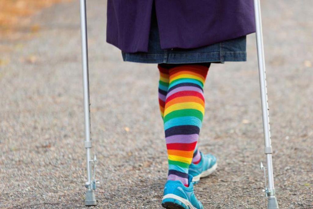 Vergrößern: Buchcover mit Beinen von hinten mit bunten Socken und Krücken