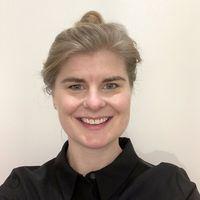 Porträt von Friderike Kuhlmann mit einem schwarzen Hemd und die blonden Haare zum einem Dutt hochgebunden