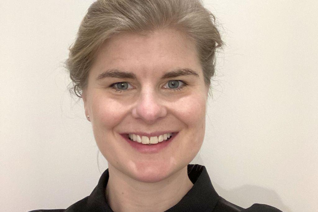 Vergrößern: Porträt von Friderike Kuhlmann mit einem schwarzen Hemd und die blonden Haare zum einem Dutt hochgebunden