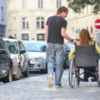 eine Frau in einem Rollstuhl wird von einem Mann begleitet