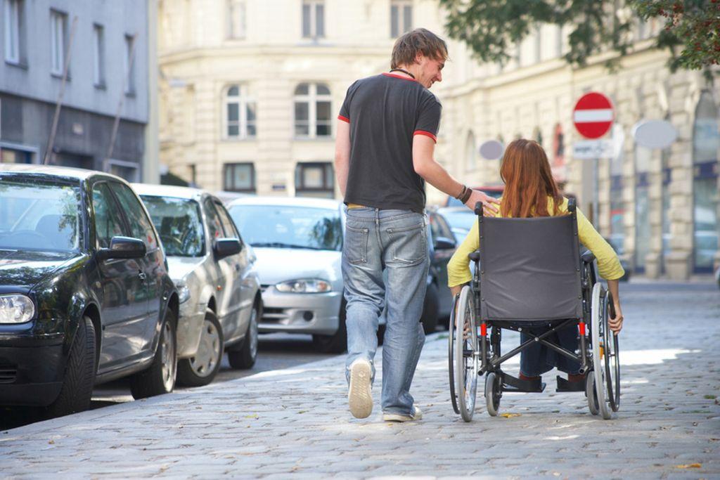 Vergrößern: eine Frau in einem Rollstuhl wird von einem Mann begleitet