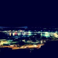 Nächtlicher Blick über die Stadt, Lichter und im Vordergrund ein Fluß