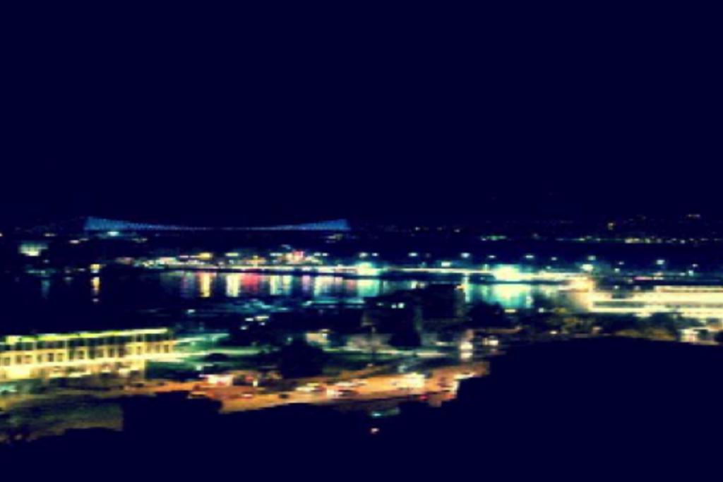 Vergrößern: Nächtlicher Blick über die Stadt, Lichter und im Vordergrund ein Fluß