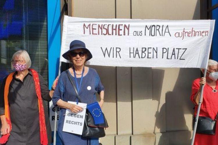 Hilde von Balluseck in einem blauen Kostüm vor einem Transparent mit der Aufschrift: Menschen aus Moria aufnehmen - Wir haben Platz