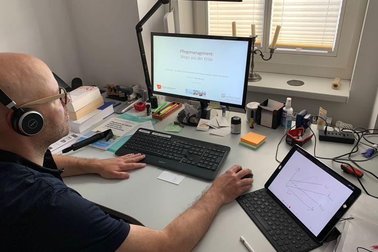 Uwe Bettig an seinem Schreibtisch vor dem Computer und mit Kopfhörern auf den Ohren