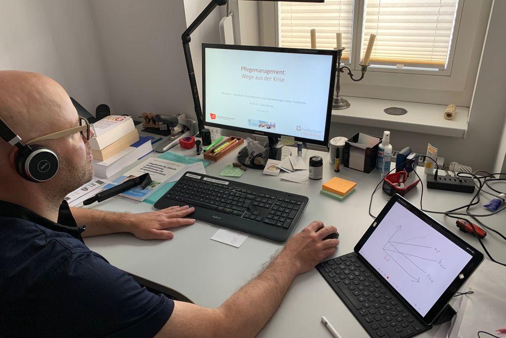 Vergrößern: Uwe Bettig an seinem Schreibtisch vor dem Computer und mit Kopfhörern auf den Ohren