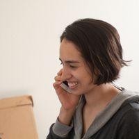 EIne Frau im Profil telefiniert lachend mit dem Handy
