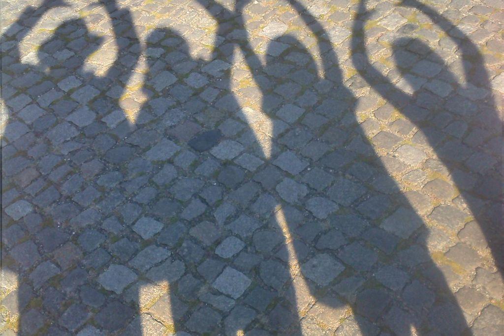 Vergrößern: Vier Schatten von Menschen auf Asphalt