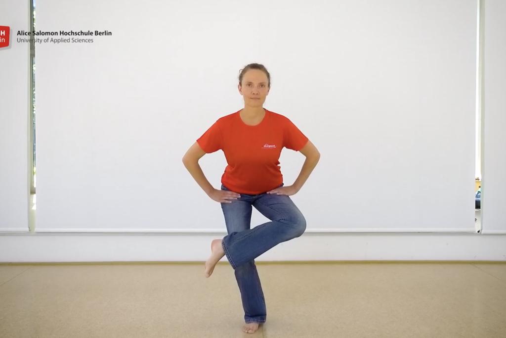 Vergrößern: Eine Frau steht im Bewegungsraum der ASH Berlin, die Hände in den Hüften, ein Bein überkreuzt im stehen das andere