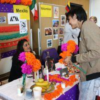 Ein Stand beim International Day- ein Besucher unterhält sich mit zwei Studentinnen, welche am Stand sitzen.
