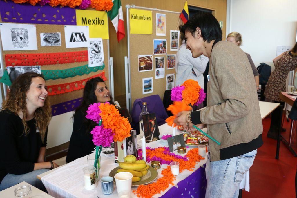 Vergrößern: Ein Stand beim International Day- ein Besucher unterhält sich mit zwei Studentinnen, welche am Stand sitzen.