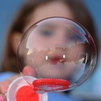 im Vordergrund eine Seifenblase, dahinter verschwommen ein Kindergesicht